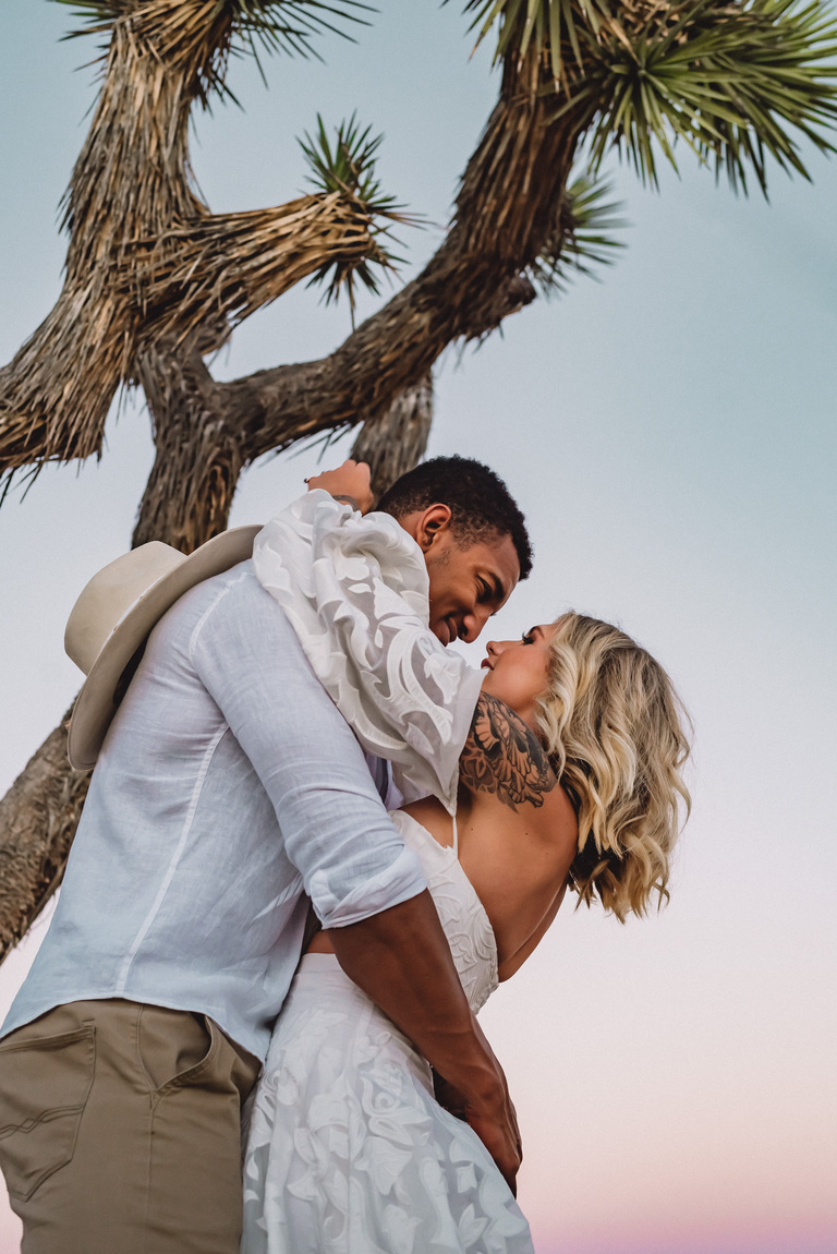 Happy couple embraces under a Joshua Tree at sunset