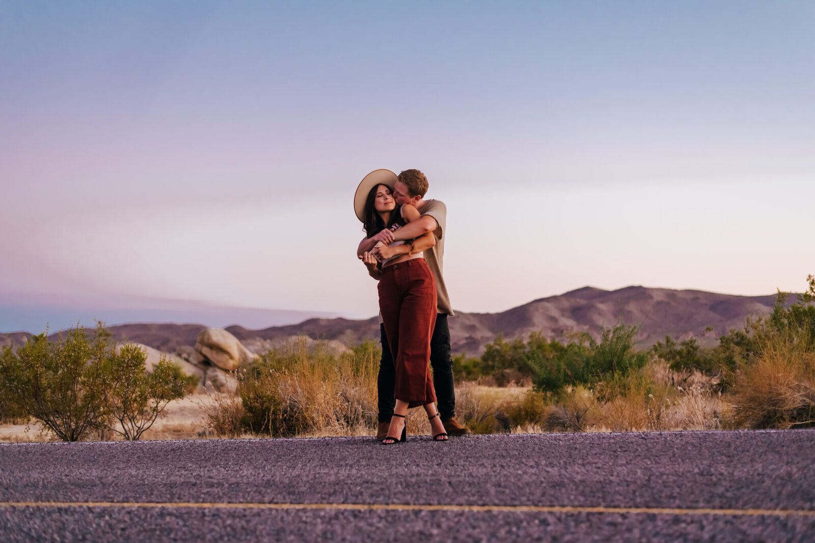 Couple hugging in front of open road