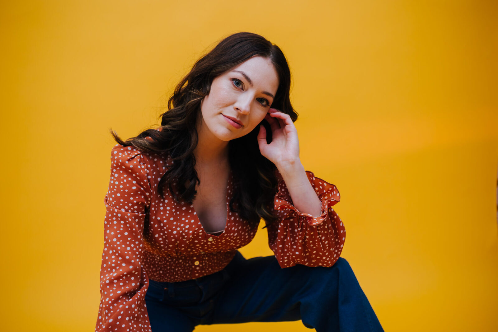 Johanna, wearing a 1970s inspired ruffle top and wide leg jeans, poses with her arm resting on her knee and tilts her head sideways with a smile