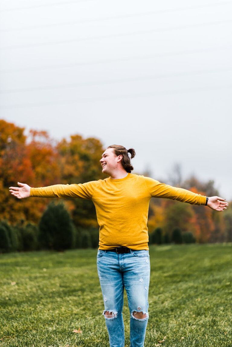 Boy in yellow sweater swings his arms around in a field of fall colors