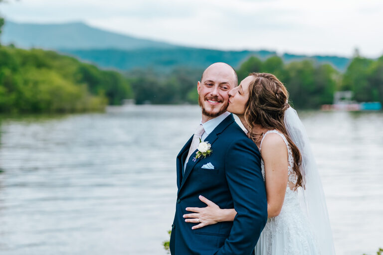 Bride kisses groom from behind as they stand in front of a mountain lake