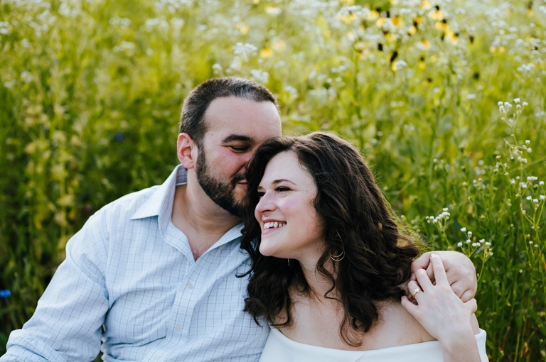 Couple sits in a grassy field and man kisses fiancé on cheek